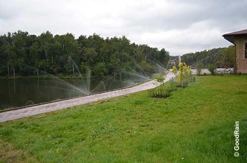 Газон орошается водой на горке перед прудом